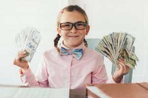 Young girl with glasses holding money