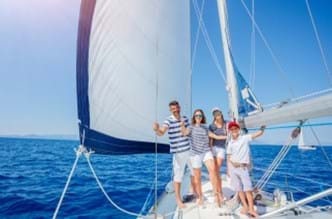 Family on a sailing boat in the ocean.