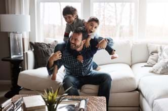 Dad sitting on the couch with his sons climbing on his shoulders.