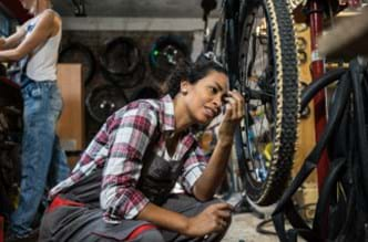 Woman working on a bicycle.