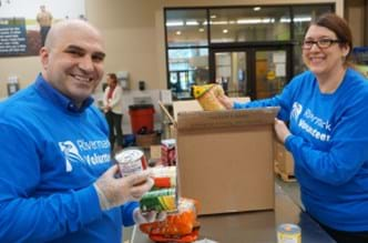 Two Rivermark employees volunteering at the Oregon Food Bank.