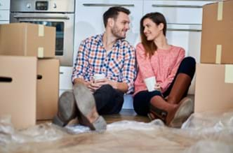 A couple sitting on the floor surrounded by boxes.