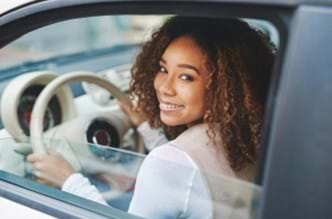 Young woman sitting in a car behind the wheel.