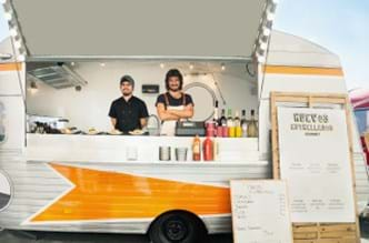 Two employees standing int he food truck smiling.