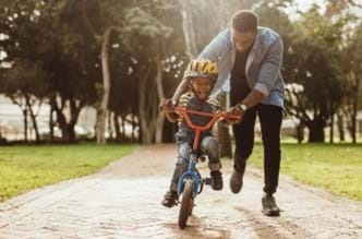 Father helping his son ride a bike without training wheels.